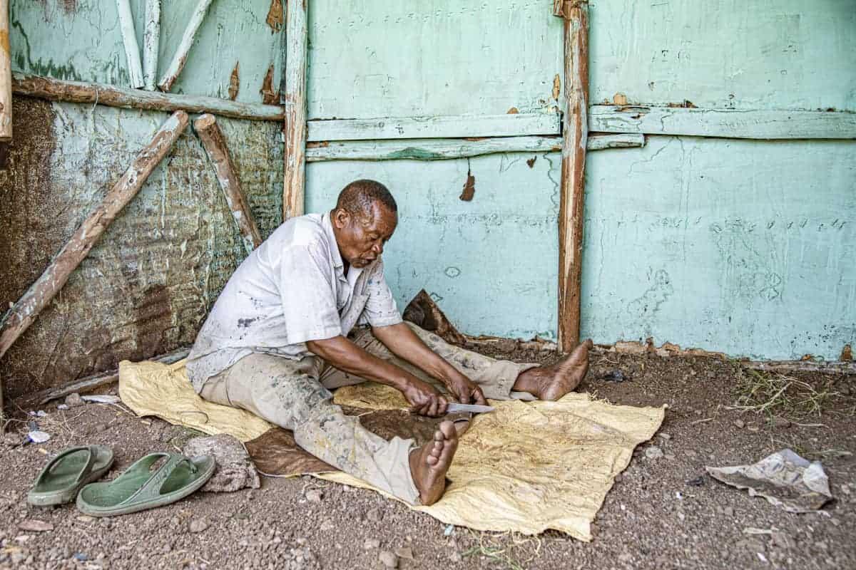 Fotoreis Afrika Tanzania Man maakt handmatig een trommel met koeienhuid