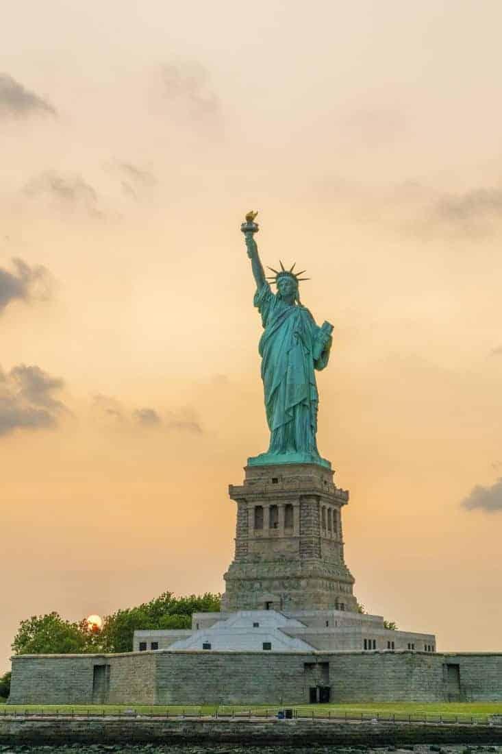 Fotoreis New York vrijheidsbeeld bij ondergaande zon staand