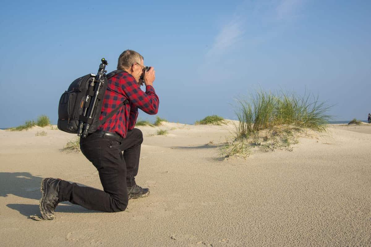 Fotoweekend Ameland - Man fotografeert knielend in het zand