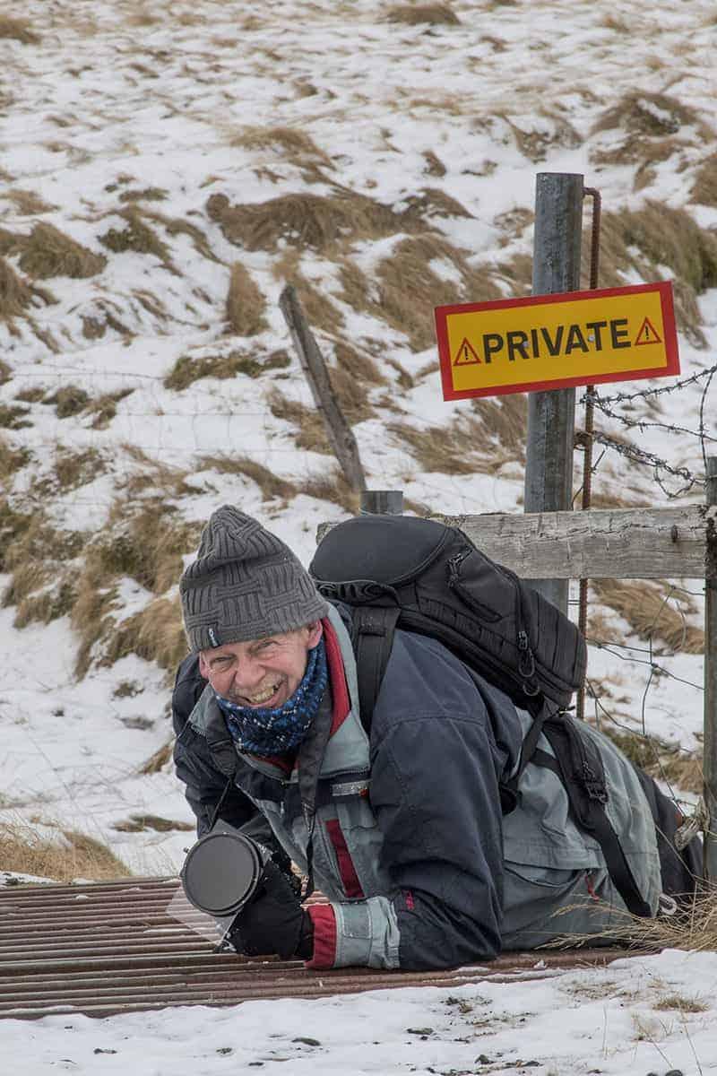Fotoreizen IJsland Henk kruipt onder hek door bij Fjardarglufur