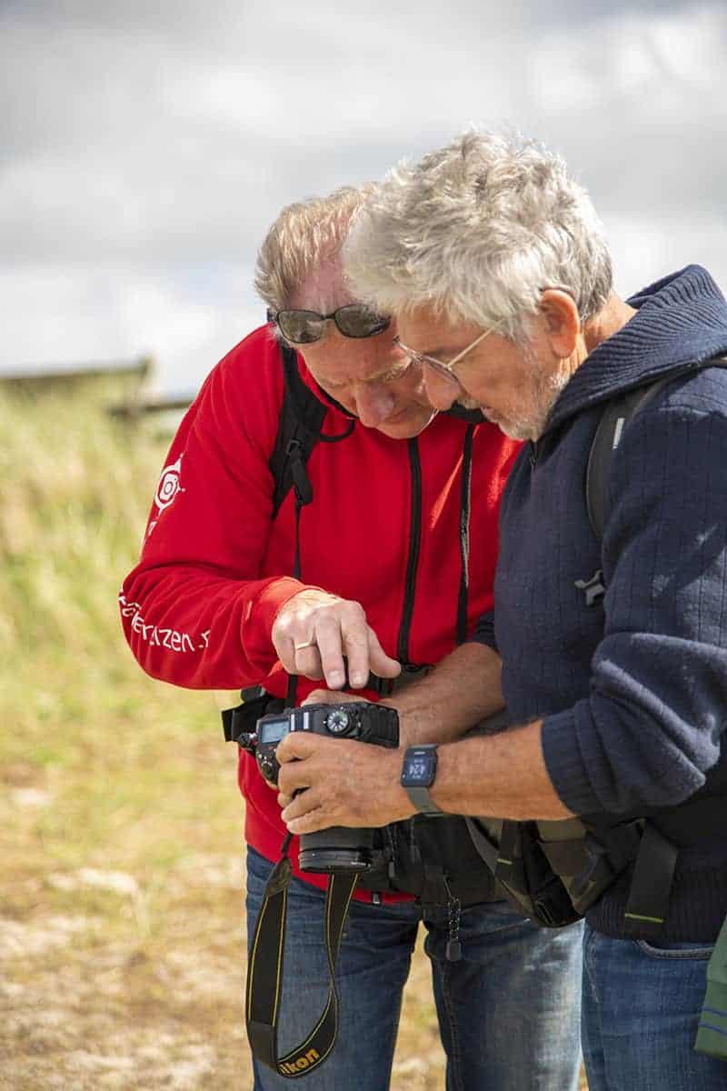 Jan Veijer geeft uitleg aan een deelnemer aan het Fotoweekend Ameland.