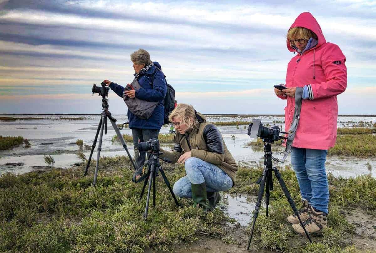 Fotoweekend Groninger Waddenkust Drie dames met statief op het wad