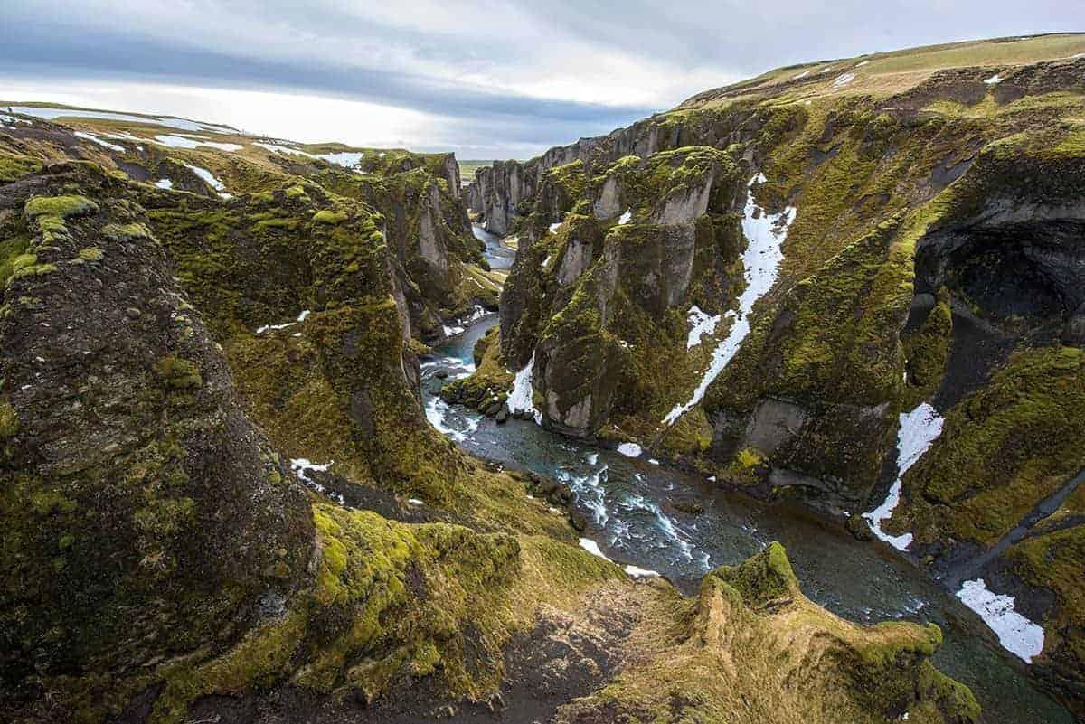 Het water baant zich een weg door de groene kloof Fjadrárgljúfur.