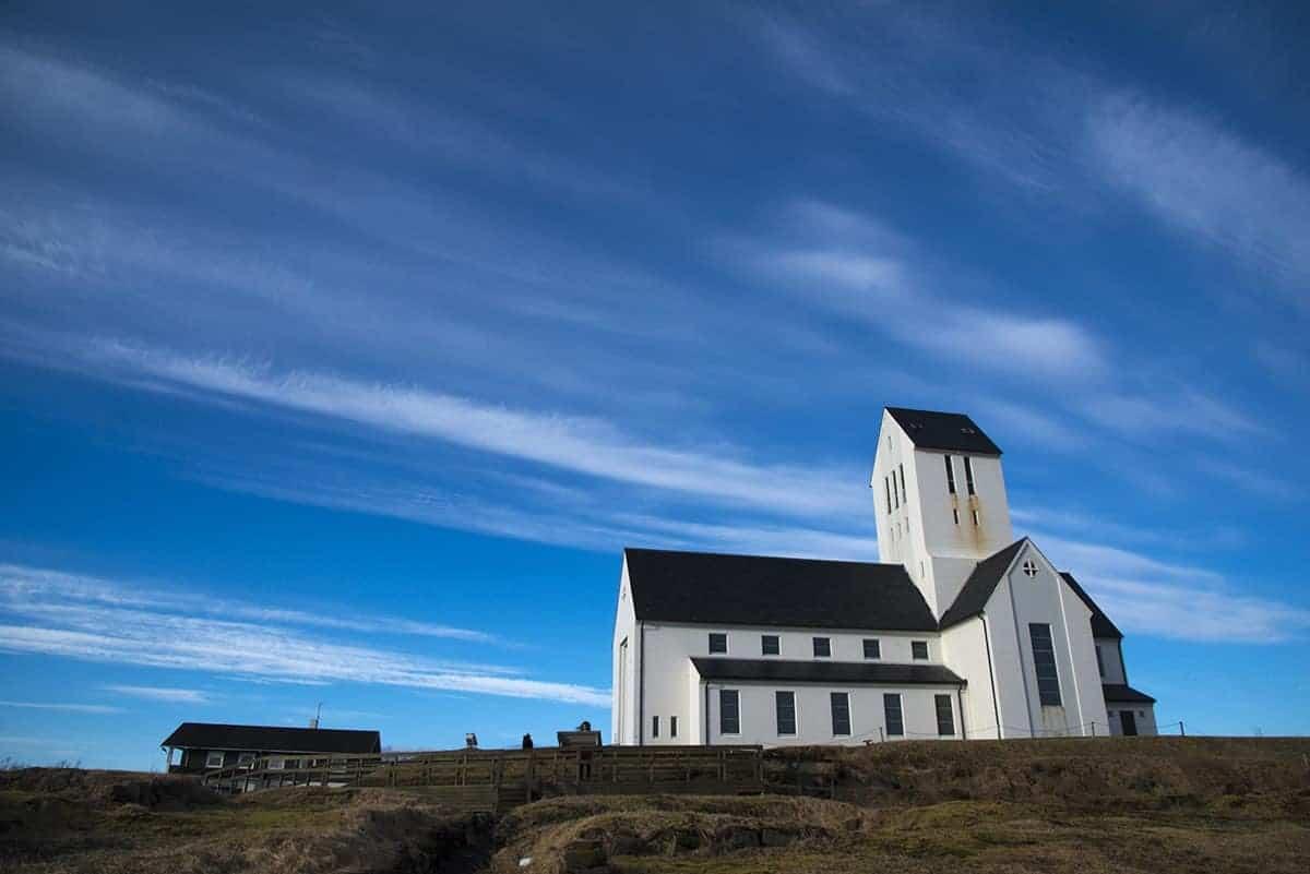 Het witte kerkje van Skalholt steekt fel af tegen de blauwe lucht.