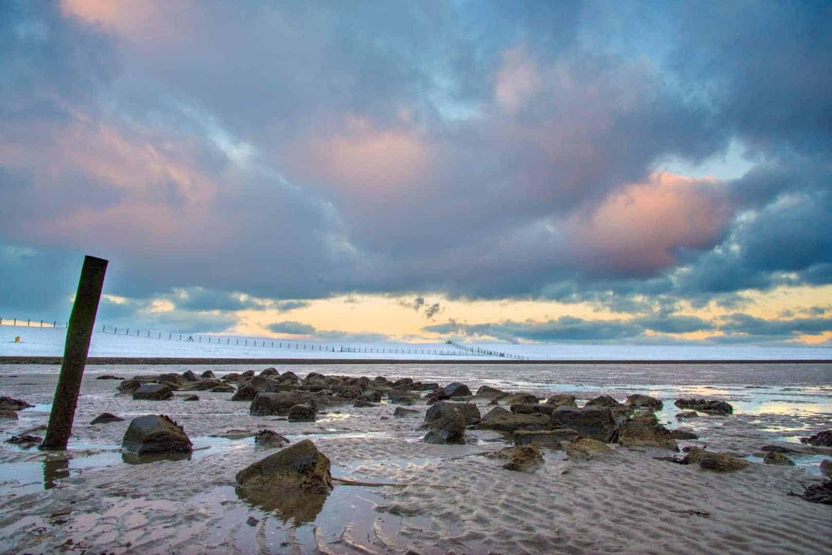 De opkomende zon boven het water van Bierum met op de achtergrond een besneeuwde dijk - workshop winterfotografie